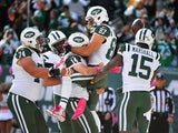 Ryan Fitzpatrick #14 of the New York Jets picks up Eric Decker #87 as he is congratulated by his teammates after scoring a third quarter touchdown against the Washington Redskins at MetLife Stadium on October 18, 2015