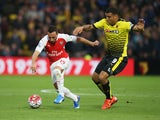 Santi Cazorla of Arsenal and Troy Deeney of Watford compete for the ball during the Barclays Premier League match between Watford and Arsenal at Vicarage Road on October 17, 2015 in Watford, England.