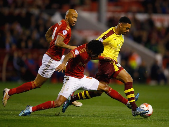 Andre Gray of Burnley battles with Ryan Mendes of Nottingham Forest during the Sky Bet Championship match between Nottingham Forest and Burnley at City Ground on October 20, 2015 in Nottingham, England.