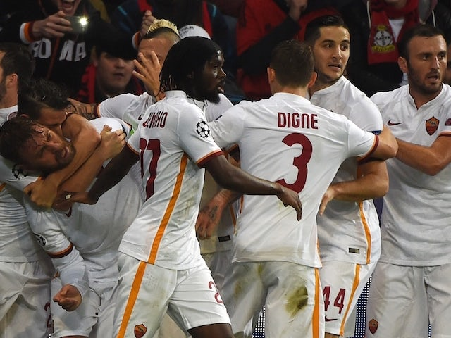 Roma�s players celebrate scoring during the Group E, first-leg UEFA Champions League football match Bayer Leverkusen vs AS Roma in Leverkusen, western Germany on October 20, 2015.