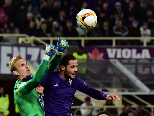 KKS Lech Poznan's goalkeeper of Bosnia Jasmin Buric (L) deflects the ball in front of Fiorentina's midfielder from Spain Mario Suarez during the UEFA Europa League group I football match Fiorentina vs Lech Poznan at the 'Artemio Franchi' stadium on Octobe
