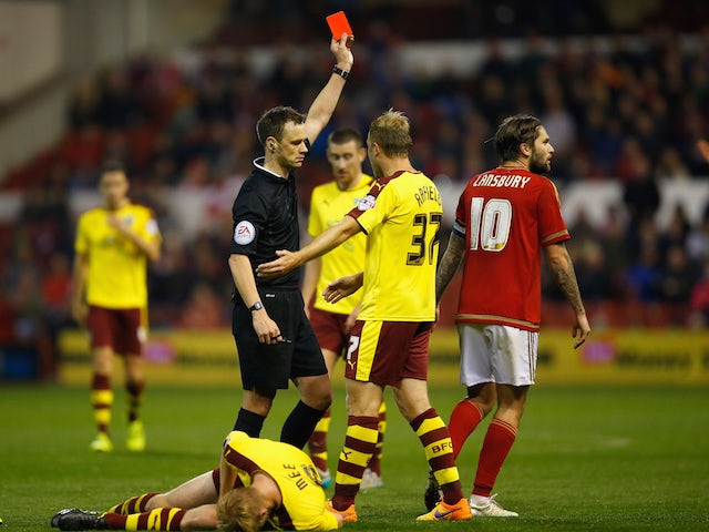 Referee Stuart Attwell sends off Henri Lansbury of Nottingham Forest during the Sky Bet Championship match between Nottingham Forest and Burnley at City Ground on October 20, 2015 in Nottingham, England.