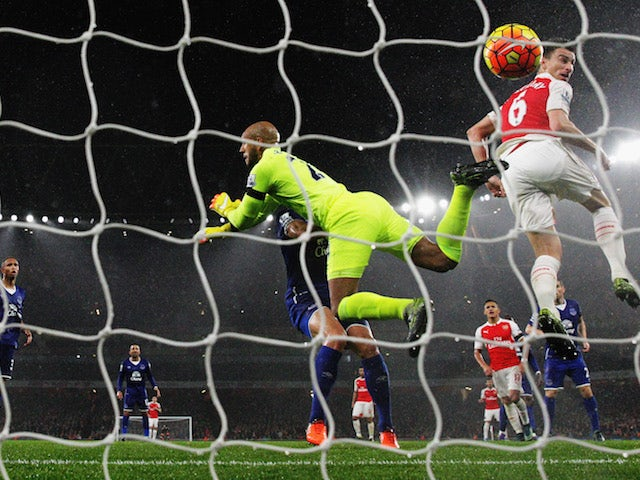 Laurent Koscielny (R) of Arsenal scores his team's second goal past Tim Howard (L) of Everton during the Barclays Premier League match between Arsenal and Everton at Emirates Stadium on October 24, 2015 in London, England.