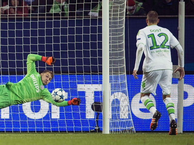 Wolfsburg's forward Bas Dost of the Netherlands (R) scores past PSV Eindhoven's goalkeeper Jeroen Zoet during the Group B, first-leg UEFA Champions League football match VfL Wolfsburg vs PSV Eindhoven in Wolfsburg, northern Germany on October 21, 2015.