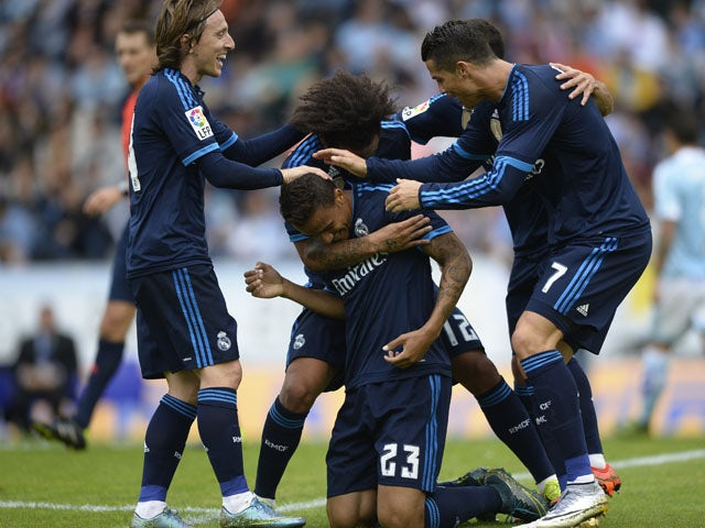 Real Madrid's Brazilian defender Danilo (C) is congratulated by teammates after scoring a goal during the Spanish league football match Celta Vigo vs Real Madrid CF at the Balaidos stadium in Vigo on October 24, 2015