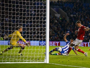 Sam Baldock of Brighton equalises despite the efforts of goalkeeper Frank Fielding and Aden Flint of Bristol City during the Sky Bet Championship match between Brighton & Hove Albion and Bristol City at Amex Stadium on October 20, 2015 in Brighton, Englan