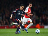 Thiago Alcantara of Bayern Munich is watched by Santi Cazorla of Arsenal during the UEFA Champions League Group F match between Arsenal FC and FC Bayern Munchen at Emirates Stadium on October 20, 2015 in London, United Kingdom.