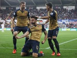 Olivier Giroud (C) of Arsenal celebrates scoring his team's first goal with his team mates Per Mertesacker (L) and Mesut Ozil (R) during the Barclays Premier League match between Swansea City and Arsenal at Liberty Stadium on October 31, 2015
