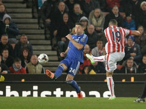 Stoke City's English-born Irish striker Jonathan Walters (R) shoots past Chelsea's English defender Gary Cahill (C) to score his team's first goal during the English League Cup fourth round football match between Stoke City and Chelsea at the Britannia St