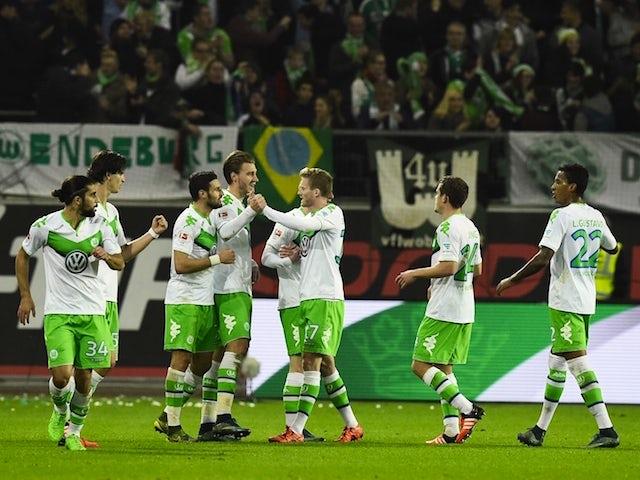 Wolfsburg's Danish forward Nicklas Bendtner (C) is congratulated by Wolfsburg's striker Andre Schuerrle (3ndR) after scoring during the German first division Bundesliga football match Wolfsburg vs Leverkusen in Wolfsburg on October 31, 2015.