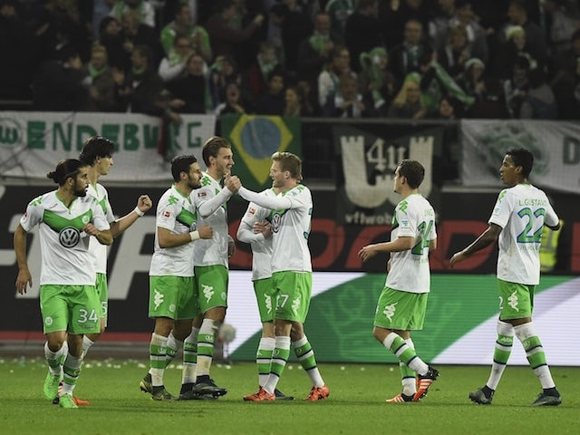 Wolfsburg's Danish forward Nicklas Bendtner (C) is congratulated by Wolfsburg's striker Andre Schuerrle (3ndR) after scoring during the German first division Bundesliga football match Wolfsburg vs Leverkusen in Wolfsburg on October 31, 2015.