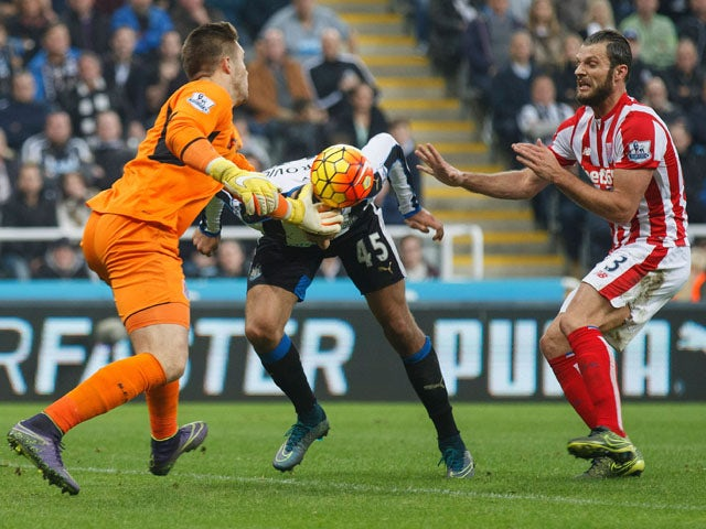 Jack Butland of Stoke City and Aleksandar Mitrovic of Newcastle United compete for the ball during the Barclays Premier League match between Newcastle United and Stoke City at St James' Park on October 31, 2015
