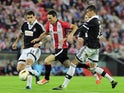 Athletic Bilbao's forward Aritz Aduriz (C) vies with Partizan's Brazilian defender Fabricio (L) and defender Lazar Cirkovic (R) during the UEFA Europa League group L football match Athletic Club Bilbao vs FK Partizan at the San Mames stadium in Bilbao on