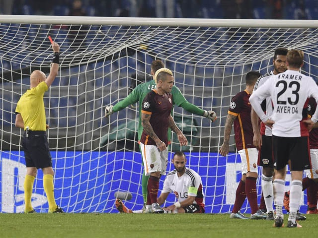 Leverkusen's Turkish defender Omer Toprak (bottom) receives a yellow card from referee Serguey Karasev during the UEFA Champions League football match AS Roma vs Bayer Leverkusen on November 4, 2015