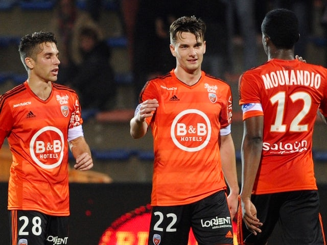 Lorient's French forward Benjamin Jeannot (C) is congratulated by Lorient's French midfielder Maxime Barthelme (L) and Lorient's Cameroonian forward Benjamin Moukandjo after scoring a goal during the French Ligue 1 match Lorient against Troyes November 7,