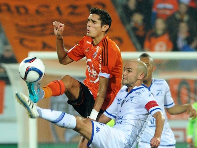 Lorient's French defender Francois Belugou (L) vies with Troyes' French midfielder Benjamin Nivet during the French Ligue 1 match Lorient versus Troyes on November 7, 2015 at the Yves Allainmat stadium in Lorient, western France.