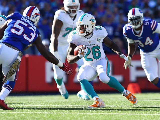 Lamar Miller #26 of the Miami Dolphins runs the ball as Nigel Bradham #53 of the Buffalo Bills defends during the first half at Ralph Wilson Stadium on November 8, 2015