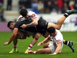 John Bateman and Gareth Widdop of England tackle Roger Tuivasa-Sheck of New Zealand during the match between England and New Zealand at the DW Stadium on November 14, 2015
