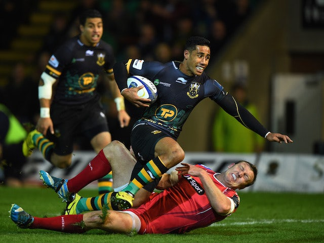 Ken Pisi of Northampton crashes over the tryline to score the opening try despite the tackle from Hadleigh Parkes of Scarlets during the European Rugby Champions Cup Pool 3 match between Northampton Saints and Scarlets at Franklin's Gardens on November 14