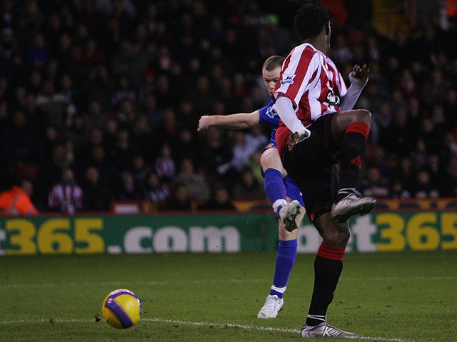 Manchester United's Wayne Rooney (L) beats Sheffield United's Claude Davis to score the second goal during their English Premiership football match at Bramall Lane, Sheffield, England, November 18 2006
