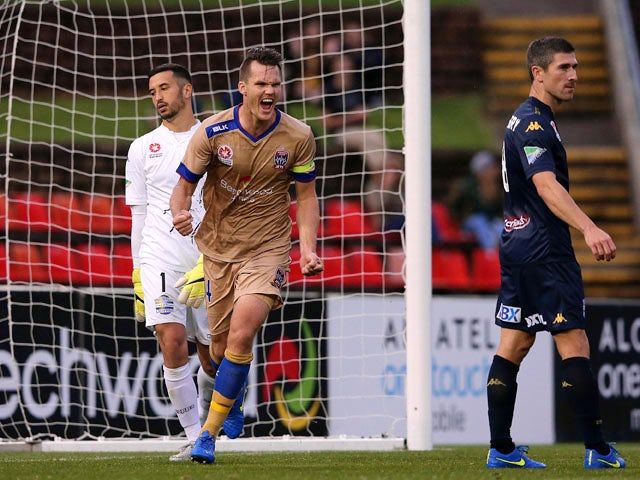 Nigel Boogaard of the Jets celebrates a goal by Milos Trifunovic with Paul Izzo and Nick Montgomery of the Mariners looking dejected in frame during the round six A-League match between the Newcastle Jets and the Central Coast Mariners at Hunter Stadium o