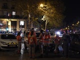Police officers and rescue workers stand near the site of a shooting near Place de la Republique square in Paris on November 13, 2015. At least 18 people were killed in several shootings and explosions in Paris today, police said.