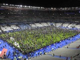 Frightened spectators wait on the pitch at the Stade de France on November 13, 2015