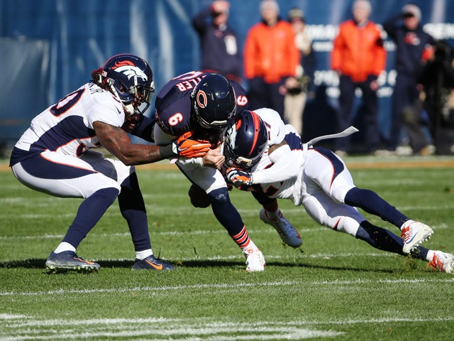 Quarterback Jay Cutler #6 of the Chicago Bears is hit by David Bruton Jr. #30 and Bradley Roby #29 of the Denver Broncos in the first quarter at Soldier Field on November 22, 2015