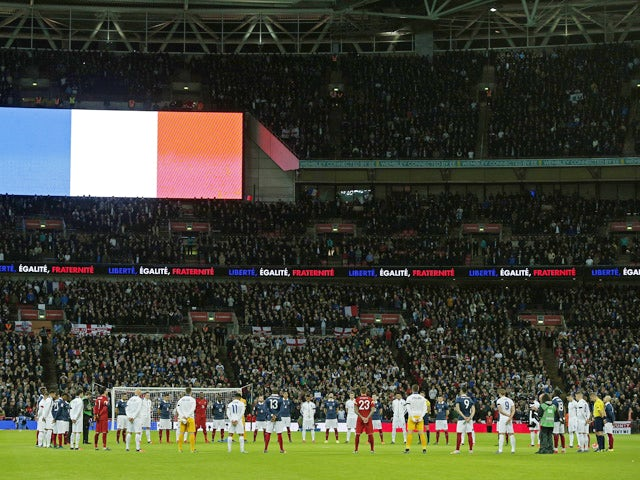 England and France squad members observe a minute's silence before the start of the friendly football match between England and France at Wembley Stadium in west London on November 17, 2015