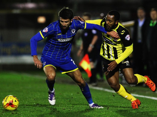 George Francomb of AFC Wimbledon and Ashley Hemmings of Dagenham and Redbridge challenge for the ball during the Sky Bet League Two match between AFC Wimbledon and Dagenham and Redbridge at The Cherry Red Records Stadium on November 24, 2015