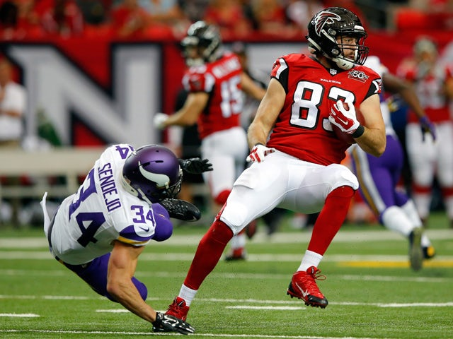 Jacob Tamme #83 of the Atlanta Falcons spins away from Andrew Sendejo #34 of the Minnesota Vikings after a catch during the first half at the Georgia Dome on November 29, 2015