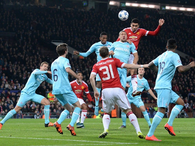 Manchester United's English defender Chris Smalling (3rd R) heads the ball during the UEFA Champions League Group B football match between Manchester United and PSV Eindhoven at the Old Trafford Stadium in Manchester, north west England on November 25, 20