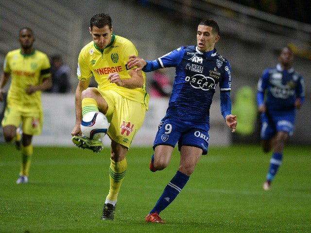 Nantes' Albanian defender Lorik Cana (L) challenges Bastia's French forward Florian Raspentino during the French L1 football match between Nantes and Bastia at the Beaujoire stadium in Nantes, western France, on November 28, 2015.