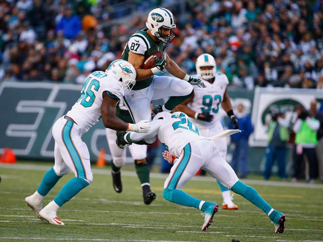 Eric Decker #87 of the New York Jets makes a catch against Reshad Jones #20, and Neville Hewitt #46 of the Miami Dolphins in the second quarter during their game at MetLife Stadium on November 29, 2015