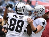 Clive Walford #88 and Derek Carr #4 of the Oakland Raiders congratulate teammate Michael Crabtree #15 on scoring a touchdown against the Tennessee Titans during the first half at Nissan Stadium on November 29, 2015
