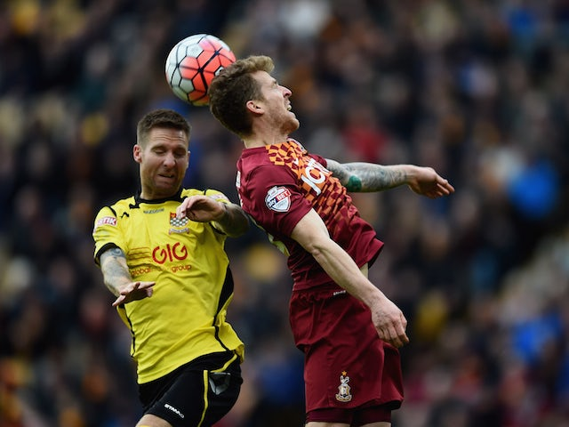 Billy Clarke of Bradford City rises for the ball with Bruce Wilson of Chesham United during The Emirates FA Cup Second Round match between Bradford City and Chesham United at Coral Windows Stadium, Valley Parade on December 6, 2015 in Bradford, England.