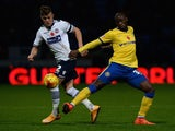 Max Clayton of Bolton Wanderers tackles Marc-Antoine Fortune of Wigan Athletic during the Sky Bet Championship match between Bolton Wanderers and Wigan Athletic at Macron Stadium on November 7, 2014