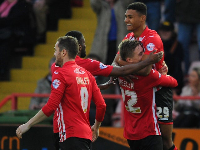 Ollie Watkins of Exeter City(R) celebrates after scoring his sides second goal during the Emirates FA Cup Second Round match between Exeter City and Port Vale at St James Park on December 6, 2015 in Exeter England.