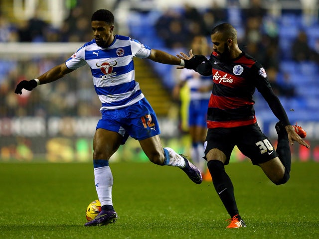 Garath McCleary of Reading holds off Sandro of QPR during the Sky Bet Championship match between Reading and Queens Park Rangers on December 3, 2015
