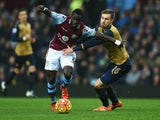 Idrissa Gueye of Aston Villa holds off Aaron Ramsey of Arsenal during the Barclays Premier League match between Aston Villa and Arsenal at Villa Park on December 13, 2015 in Birmingham, England.