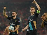 Per Mertesacker of Arsenal and Olivier Giroud of Arsenal celebrate at the end of Arsenal's win in the UEFA Champions League Group F match between Olympiacos FC and Arsenal FC at Karaiskakis Stadium on December 9, 2015 in Piraeus, Greece.