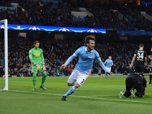 Manchester City's Spanish midfielder David Silva (C) wheels away to celebrate scoring the opening goal during the UEFA Champions League Group D football match between Manchester City and Borussia Moenchengladbach at the Etihad Stadium in Manchester, north