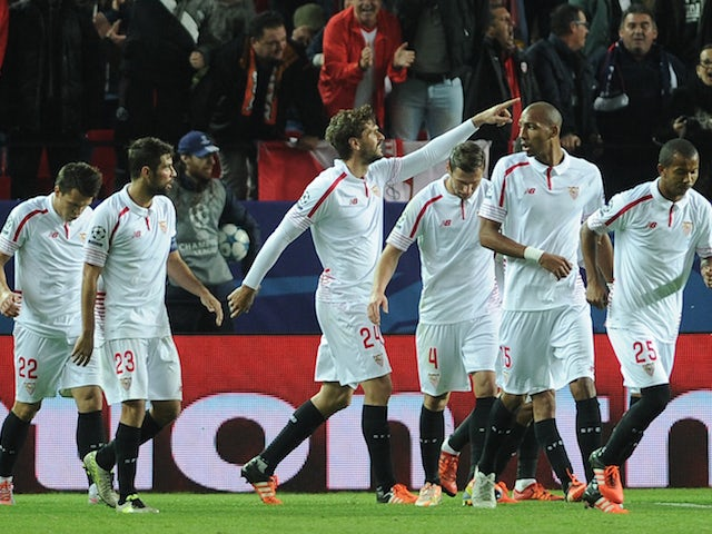 Sevilla's Spanish forward Fernando Llorente (C) celebrates with teammates after scoring a goal during the UEFA Champions League Group D football match Sevilla FC vs Juventus at the Ramon Sanchez Pizjuan stadium in Sevilla on December 8, 2015.