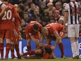 Liverpool's English midfielder James Milner (L) and Liverpool's Slovakian defender Martin Skrtel (R) aid Liverpool's Croatian defender Dejan Lovren (C) who was injured in a challenge with West Bromwich Albion's English midfielder Craig Gardner during the