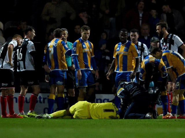 Jason Leutwiler of Shrewsbury is injured in a clash with Andy Monkhouse of Grimsbury during the Emirates FA Cup second round match between Grimsby Town and Shrewsbury Town at Blundell Park on December 7, 2015