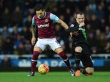 Mauro Zarate of West Ham United and Glenn Whelan of Stoke City compete for the ball during the Barclays Premier League match between West Ham United and Stoke City at the Boleyn Ground on December 12, 2015