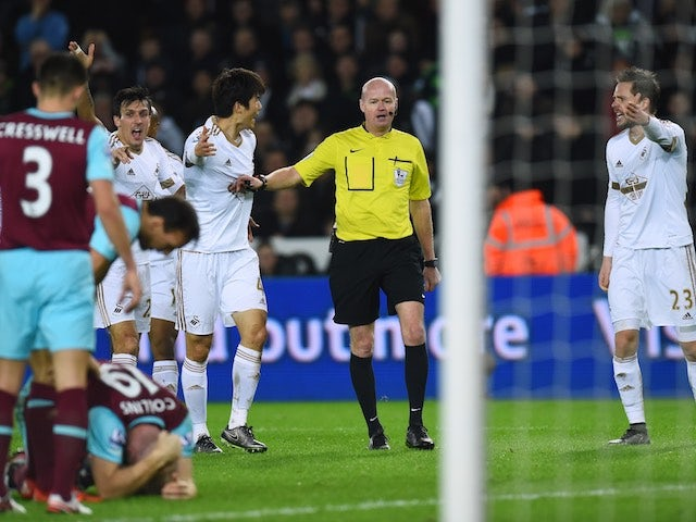 Swansea players appeal to referee Lee Mason after West Ham's James Collins appeared to handle the ball on December 20, 2015
