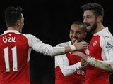 Olivier Giroud celebrates with Arsenal teammates Mesut Ozil and Theo Walcott after scoring against Manchester City in the Premier League on December 21, 2015