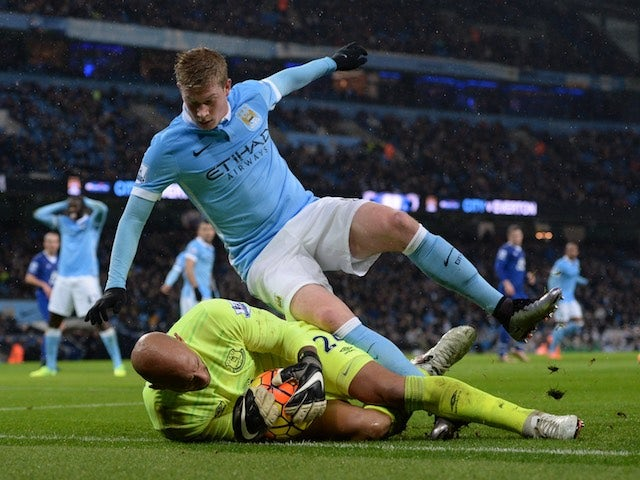 Kevin de Bruyne topples over Tim Howard during the game between Man City and Everton on January 13, 2016