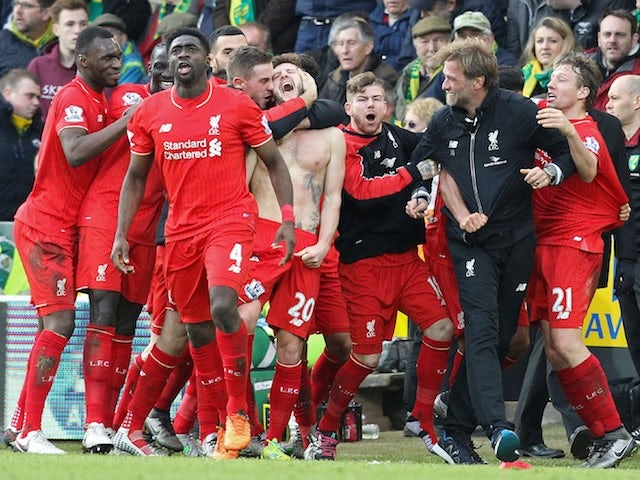 Adam Lallana celebrates with Liverpool teammates and manager Jurgen Klopp after scoring the winner against Norwich City on January 23, 2016
